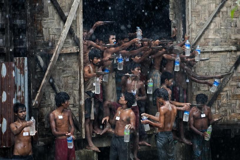 ชาวโรฮีนจาซึ่งถูกพบกลางทะเลกำลังใช้จานและขวดพลาสติกรองรับน้ำฝนไว้บริโภคที่ศูนย์พักพิงชั่วคราวในรัฐยะไข่ ประเทศพม่า เมื่อวันที่ 4 มิ.ย. ปี 2015 ความทุกข์ทรมานของชาวมุสลิมโรฮีนจาซึ่งถูกทางการพม่าปฏิเสธความเป็นพลเมือง กลายเป็นวิกฤตด้านมนุษยธรรมครั้งใหญ่ในเอเชียตะวันออกเฉียงใต้ที่ทั่วโลกเพ่งเล็ง