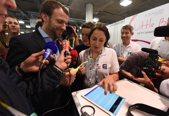 Las Vegas, Nevada, UNITED STATES: French Economy Minister Emmanuel Macron (L) reacts as E. Sensory founder Christel Le Coq (R) activates The Little Bird smart vibrator Macron is holding by reading an erotic story on her e-reader, during Macrons visit to French technology startups, at the CES 2016 consumer electronics show in Las Vegas, Nevada, January 7, 2015. AFP PHOTO/Robyn Beck