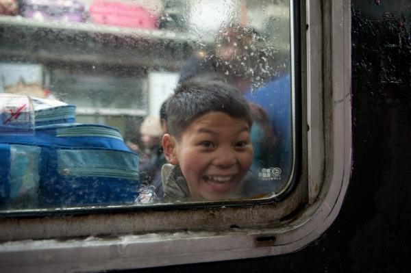 เด็กชายนั่งอยู่ในตู้ขบวนที่เตรียมแล่นออกจากสถานีรถไฟปักกิ่งตะวันตก (23 ม.ค. 2559/ ภาพ รอยเตอร์ส)