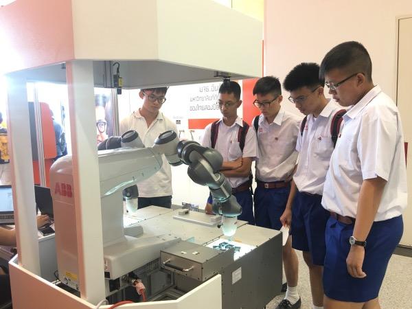 เด็กนักเรียนชมการทำงานหุ่นยนต์ประกอบชิ้นส่วน