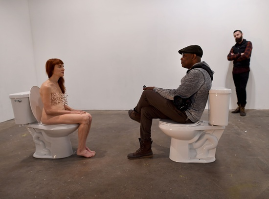"""New York, State of New York: Graphic content/Conceptual artist and comedian Lisa Levy sits nude on a toilet facing a clothed participant on another toilet during Levys performance art show titled """"The Artist Is Humbly Present"""" at the Christopher Stout Gallery January 31, 2016 in the Bushwick section of New York. AFP/Timothy A. Clary"""