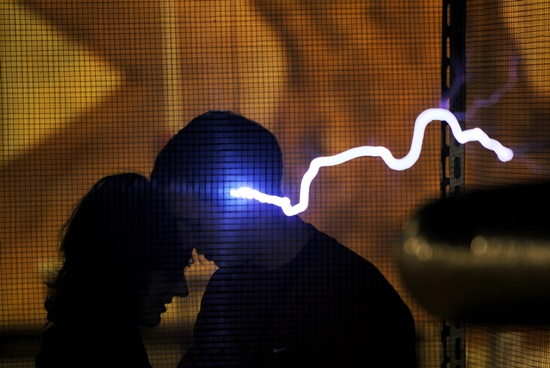 Minsk: This photo taken late on February 13, 2016 shows a couple sharing a tender moment by a Faraday cage displaying electrical sparks of Tesla coil, on the eve of Valentines Day at the Elemento Science Museum in Minsk. AFP/Sergei Gapon