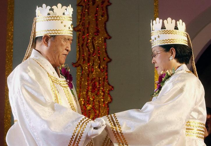 ซัน เมียง มุน และ ฮัก จา ฮัน ผู้เป็นภรรยา ประสานมือเพื่ออวยพรคู่บ่าวสาวในพิธีสมรสหมู่ของโบสถ์แห่งความสามัคคี ณ สนามกีฬากรุงโซล เมื่อปี 2002 (แฟ้มภาพ)