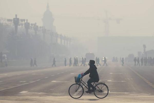 หญิงชาวจีนปั่นจักรยานใกล้กับจัตุรัสเทียนอันเหมิน กรุงปักกิ่ง ในวันที่หมอกพิษปกคลุมหนาทึบ (21 ธ.ค. 2558/ ภาพ เอเอฟพี)