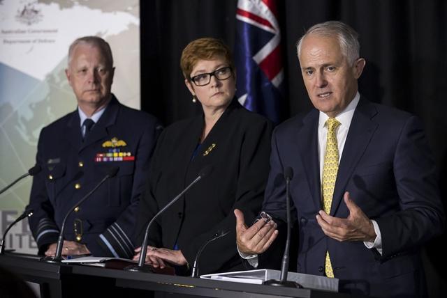 """<i>ภาพที่เผยแพร่โดยกองทัพออสเตรเลีย แสดงให้เห็น นายกรัฐมนตรีมัลคอล์ม เทิร์นบูลล์ (ขวา) กำลังแถลงข่าว ในงานเปิดตัวเอกสาร """"สมุดปกขาวกลาโหม"""" ประจำปี 2016 โดยที่มีรัฐมนตรีกลาโหม มาไรซ์ เพย์น (กลาง) ยืนอยู่ข้างๆ  ณ โรงเรียนทหารรวมเหล่าออสเตรเลีย, กรุงแคนเบอร์รา เมื่อวันพฤหัสบดี (25 ก.พ.) </i>"""