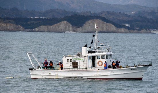 AT SEA, JAPAN: This photo taken on February 22, 2016 shows Greenpeace researchers gathering samples during their latest marine survey, on a chartered fishing boat, by sending down a remote-controlled vehicle attached with a camera and a scooper, some 20 kms south off the coast of the troubled Fukushima Daiichi nuclear power plant. Greenpeace is surveying waters near the Fukushima plant, dredging up sediment from the ocean floor to check both for radiation hotspots as well as places that are not contaminated. AFP PHOTO/Toshifumi Kitamura