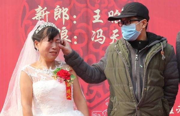 นายหวัง เผยหง เช็ดน้ำตาของผู้เป็นแม่ในพิธีแต่งงาน ที่เขาระดมทุนจากโลกออนไลน์มาจัดขึ้นเมื่อวันศุกร์ที่ 26 ก.พ. 2559 (ภาพ สื่อจีน)