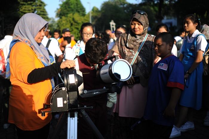 นักเรียนในมาเลเซียส่องกล้องโทรทรรศน์ที่ติดฟิล์มป้องกันอันตรายจากแสงอาทิตย์ (MOHD RASFAN / AFP)
