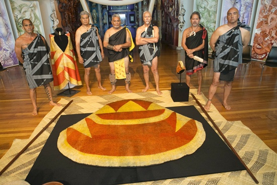 Wellington: This handout photo taken on March 11, 2016 and received from New Zealands national museum Te Papa shows Kiai or guardians standing with Indigenous Hawaiian garments gifted to Captain James Cook shortly before he was killed in the Pacific islands 237 years ago which were handed back to their traditional owners at a ceremony in Wellington on March 11, 2016. Described as priceless by New Zealands national museum Te Papa, the mahiole (feathered helmet) and ahu ula (feathered cloak) were given to Cook in 1779 during the famous British explorers last voyage. AFP/Te Papa/Norm Heke