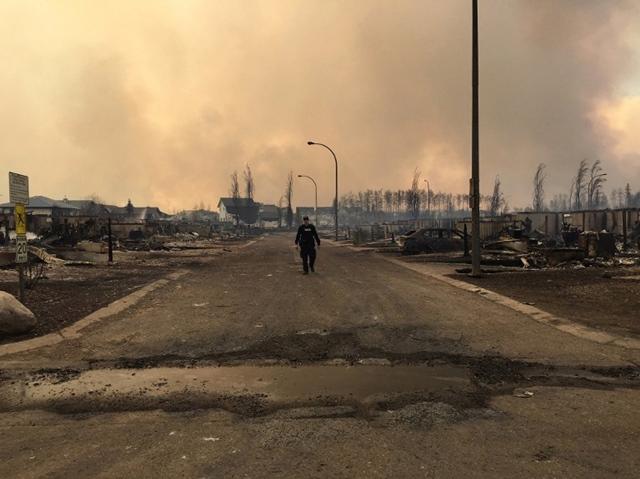 <i>ตำรวจเดินไปตามถนนผ่านบ้านเรือนที่ถูกพระเพลิงเผาผลาญ ในเมืองฟอร์ต แมคเมอร์เรย์  ตามภาพนี้ที่เผยแพร่โดยสำนักงานตำรวจแคนาดาแห่งรัฐแอลเบอร์ตาเมื่อวันพฤหัสบดี (5 พ.ค.) เมืองฟอร์ต แมคเมอร์เรย์  กลายเป็นเมืองร้างภายหลังทางการสั่งอพยพประชาชนกว่า 80,000 คนให้หลบหนีไฟป่าที่อาละวาดหนัก </i>