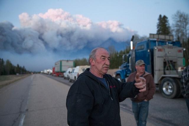 <i>คนขับรถบรรทุกรอให้เจ้าหน้าที่ยืนยันว่าปลอดภัยและอนุญาตให้เดินทางได้ เพื่อนำเอาสิ่งของซึ่งใช้ในการดับไฟเข้าไปยังเมืองเล็กแห่งหนึ่ง ที่อยู่นอกเมืองฟอร์ต แมคเมอร์เรย์, รัฐแอลเบอร์ตา, แคนาดา เมื่อวันพฤหัสบดี (5 พ.ค.) </i>