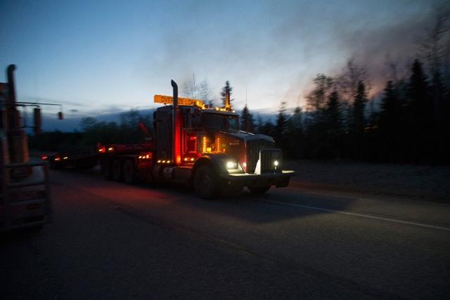 <i>รถบรรทุกขนข้าวของใช้ในการดับไฟ ขับผ่านกลุ่มควันที่ลอยออกมาจากกองเพลิงข้างทางเมื่อวันพฤหัสบดี (5 พ.ค.) ในบริเวณใกล้ๆ เมืองฟอร์ต แมคเมอร์เรย์ </i>