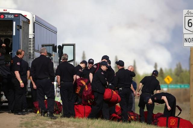 <i>พนักงานดับเพลิงรวมตัวกันที่ทางหลวงหมายเลข 63 ใกล้ๆ เมืองฟอร์ต แมคเมอร์เรย์ เมื่อวันพฤหัสบดี (5 พ.ค.) </i>