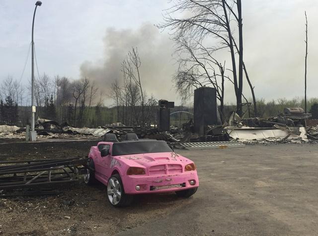 <i>รถยนต์สีชมพูดสด โดดเด่นท่ามกลางบ้านเรือนที่ถูกทำลายยับเยิน ภายหลังพระเพลิงเผาผลาญพื้นที่ย่านวอเตอร์เวย์ส ในเมืองฟอร์ต แมคเมอร์เรย์ (ภาพจากสมาคมพนักงานดับเพลิงรัฐแอลเบอร์ตา) </i>