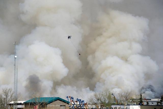 <i>เฮลิคอปเตอร์ผจญเพลิง ทำงานท่ามกลางกลุ่มควันจากไฟป่าที่เผาผลาญหลายย่านของเมืองฟอร์ต แมคเมอร์เรย์ เมื่อวันพุธ (4 พ.ค.) (ภาพจากเจ้าหน้าที่รัฐบาลรัฐแอลเบอร์ตา)</i>