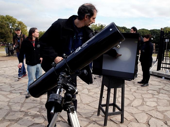 ชายในอาร์เจนตินา ชี้ตำแหน่งภาพดาวพุธบนภาพที่สะท้อนจากกระจก ระหว่างชมปรากฏการณ์ดาวพุธผ่านหน้าดวงอาทิตย์ ( REUTERS/Marcos Brindicci)