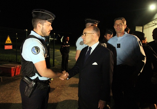 Laloubere, France: French Interior minister Bernard Cazeneuve (C) shakes hands with a policeman on May 20, 2016 in Laloubere as he arrives to pay tribute to the four gendarmes killed in a helicopter crash. The helicopter crashed on May 20 in the mountainous area of the Pyrenees during a training flight, according to the Gendarmerie. AFP/Laurent Dard