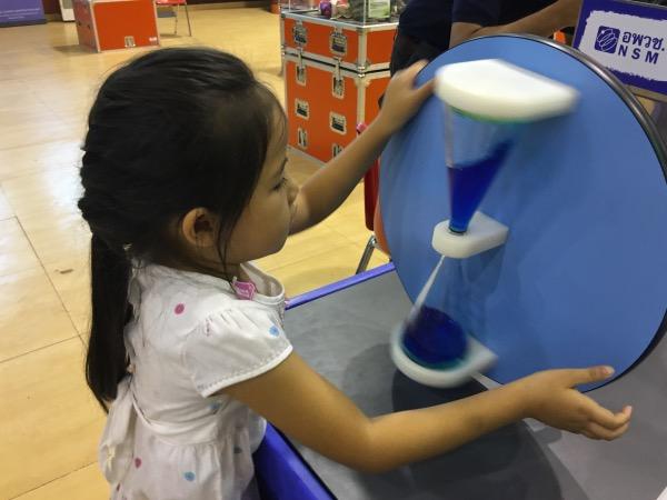 เด็กหญิงชาวลาวหมุนแป้นรูปทรงเรขาคณิต