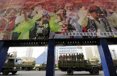 """รถบรรทุกเจ้าหน้าที่ปราบจลาจลกำลังทยอยเข้ามายังเมืองอูหลู่มู่ฉีในปี 2551  ผ่านป้ายโฆษณาชวนเชื่ออันมหึมา ฉายภาพ """"สังคมกลมกลืน"""" ที่มีชาวจีนฮั่น กับชนชาติส่วนน้อยมุสลิมอุยกูร์ อยู่ร่วมกันอย่างเต็มไปด้วยรอยยิ้ม-เอเอฟพี"""