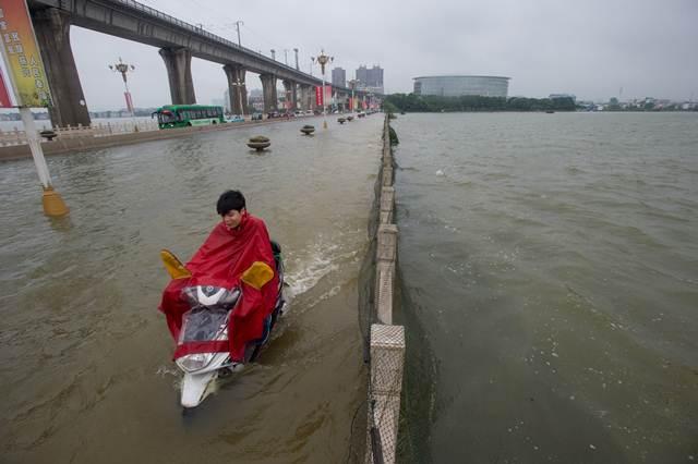 ชายจีนขี่สกูปเตอร์บนสะพานที่น้ำท่วมในอู่ฮั่น ภาพเมื่อวันที่ 2 ก.ค. (ภาพ เอเอฟพี)
