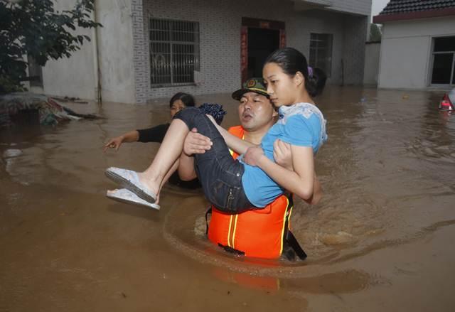 เจ้าหน้าที่หน่วยกู้ภัยกำลังช่วยหญิงจีนออกจากบ้านที่โดนน้ำท่วมในซินโจว มณฑลหูเป่ย เมื่อวันที่ 1 ก.ค. (ภาพ เอเอฟพี)
