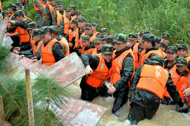 เจ้าหน้าที่จากหน่วยกองกำลังกึ่งทหารกำลังสร้างแนวป้องกันน้ำท่วมในเมืองหนันจิง มณฑลเจียงซู เมื่อวันที่ 3 ก.ค. (ภาพ รอยเตอร์ส)