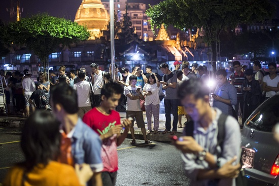 Yangon, Yangon division: In this picture taken on August 10, 2016, residents of Yangon gather in the street near the city hall to play Pokemon Go on their smartphones. While Myanmar was officially excluded from the August 6 Pokemon Go launch in Southeast Asia, game fanatics have discovered Pokemon Go is active in Yangon, immediately attracting crowds of players and turning several historical landmarks into hunting grounds. AFP/Ye Aung Thu