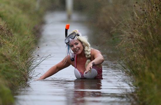 Llanwrtyd Wells, United Kingdom: A competitor takes part in the World Bog Snorkelling Championships in Waen Rhydd peat bog at Llanwrtyd Wells, south Wales on August 28, 2016. AFP/Geoff Caddick