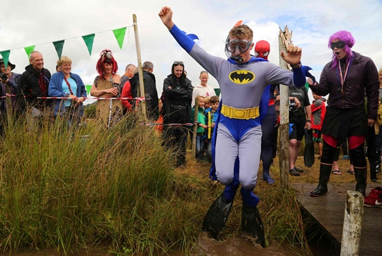Llanwrtyd Wells, United Kingdom: A man dressed as Batman jumps into the water as he takes part in the World Bog Snorkelling Championships in Waen Rhydd peat bog at Llanwrtyd Wells, south Wales on August 28, 2016. AFP/Geoff Caddick