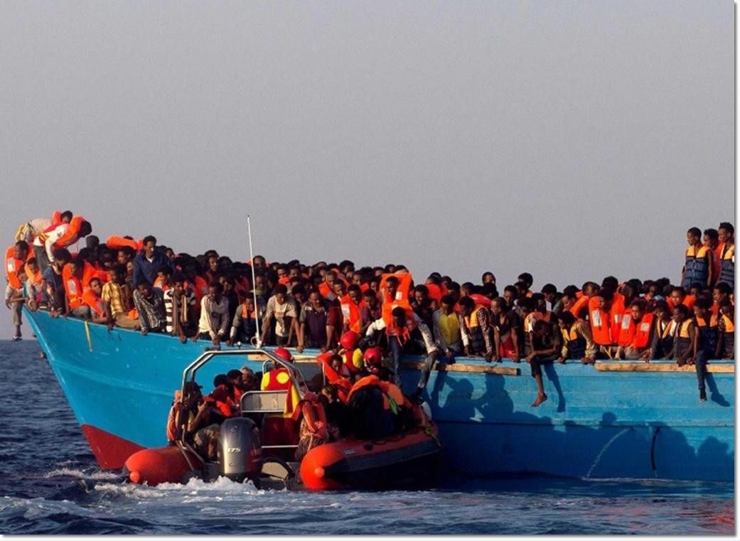 เรือเจ้าหน้าที่กู้ภัยหน่วยงานเอ็นจีโอสัญชาติสเปน โปรแอคติวา(Proactiva) วิ่งตรงเข้ามาหาเรือที่แน่นขนัดไปด้วยผู้อพยพจากเอริเทรีย ลอยลำนอกชายฝั่งลิเบียกลางทะเลเมดิเตอร์เรเนียนในวันจันทร์(29 ส.ค) ภาพจากรอยเตอร์