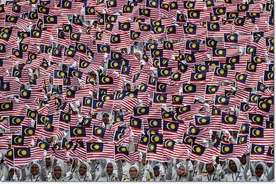 นักเรียนมาเลย์จำนวนมากต่างโบกธงชาติมาเลเซียอย่างพร้อมเพรียงในการฉลองวันได้รับเอกราชครั้งที่ 59  จากอังกฤษกลางจัตุรัสเอกราชในกรุงกัวลาลัมเปอร์ในวันพุธ(31 ส.ค) ภาพจากเอเอฟพี