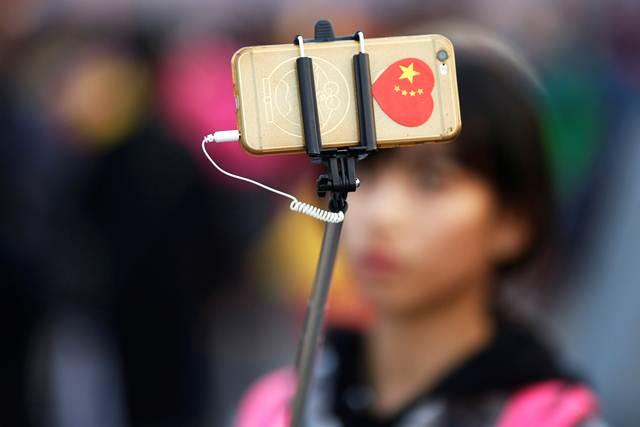 ชาวจีนถ่ายภาพเซลฟี่ที่จัตุรัสเทียนอันเหมิน ระหว่างเข้าร่วมการฉลองวันชาติจีน ครบรอบ 67 ปี เมื่อวันที่ 1 ต.ค. (ภาพ รอยเตอร์ส)
