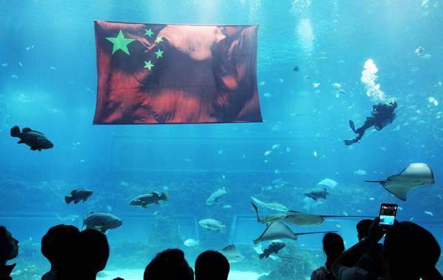 ธงประจำชาติจีนถูกนำมาแสดงใต้น้ำที่พิพิธภัณฑ์สัตว์น้ำ เพื่อฉลองวันชาติจีนในเมืองหนังชาง มณฑลเจียงซี  ภาพเมื่อวันที่ 30 ก.ย. 2016 (ภาพ รอยเตอร์ส)