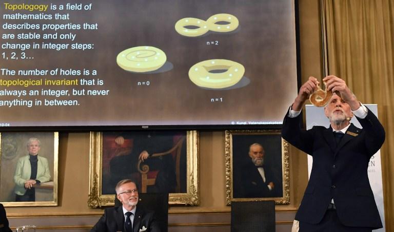 ธอร์ส ฮานส์ ฮานสัน (Thors Hans Hansson) สมาชิกคณะกรรมการรางวัลโนเบลสาขาฟิสิกส์ อธิบายถึงผลงานที่ได้รับรางวัลปีล่าสุด ขณะที่  โกรังค์ ฮานสัน (Göran K. Hansson) เลขาธิการประจำ  ราชบัณฑิตสภาด้านวิทยาศาสตร์แห่งสวีเดน (The Royal Swedish Academy of Sciences) รับฟังอยู่ด้านหลังระหว่างแถลงข่าว (JONATHAN NACKSTRAND / AFP )