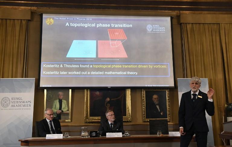 ธอร์ส ฮานส์ ฮานสัน (Thors Hans Hansson) สมาชิกคณะกรรมการรางวัลโนเบลสาขาฟิสิกส์ อธิบายถึงผลงานที่ได้รับรางวัลปีล่าสุด ขณะที่ (กลาง) โกรังค์ ฮานสัน (Göran K. Hansson) เลขาธิการประจำ ราชบัณฑิตสภาด้านวิทยาศาสตร์แห่งสวีเดน (The Royal Swedish Academy of Sciences) และ นิลส์ มาร์เทนส์สัน (Nils Martensson) รักษาการประธานคณะกรรมการรางวัลโนเบลสาขาฟิสิกส์ (ซ้าย) รับฟังอยู่ด้านหลังระหว่างแถลงข่าว (JONATHAN NACKSTRAND / AFP )