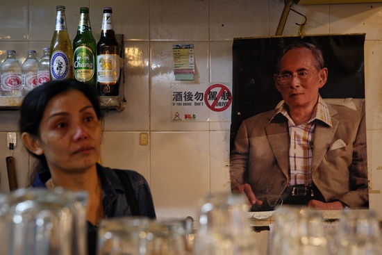 Hong Kong: Restaurant owner Vivian Tsang, from Thailand, looks on next to a portrait of the late Thai King Bhumibol Adulyadej in her restaurant in Hong Kong on October 13, 2016. King Bhumibol Adulyadej, long a unifying figure in politically fractious Thailand, died on October 13, 2016 and uncertainty over the succession quickly arose as his crown prince reportedly sought a delay in taking over. The death of the 88-year-old Bhumibol, the worlds longest-reigning monarch, removed a revered father figure in a country where political tensions are still raw two years after a military coup. AFP/Aaron Tam