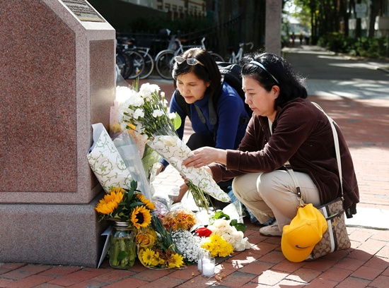 Cambridge, Massachusetts, United States: Nayara Amatquanich (C) and Anchulee Astadonwu, both tourists from Thailand, lay flowers and a candle at King Bhumibol Adulyadej Square on October 13, 2016 in Cambridge, Massachusetts. Thailands King Bhumibol Adulyadej, the worlds longest-reigning monarch, has died at the age of 88, the palace announced on October 13, leaving a divided nation bereft of a rare figure of unity. AFP/Mary Schwa