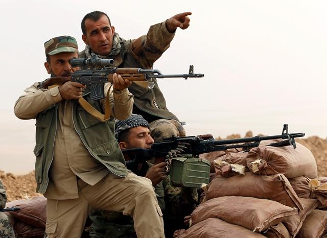 """<i>นักรบ """"เพชเมอร์กา"""" ของชาวเคิร์ดอิรัก เล็งปืนขณะสู้รบกับพวกไอเอสที่หมู่บ้านทอปซาวา เมื่อวันจันทร์ (24 ต.ค.) หมู่บ้านแห่งนี้ซึ่งอยู่ไม่ห่างจากเมืองโมซุล ตั้งอยู่ใกล้ๆ เขตปกครองของชาวเคิร์ดอิรัก </i>"""