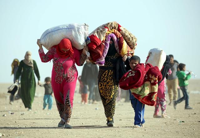 <i>ผู้ลี้ภัยชาวอิรัก ซึ่งหลบหนีออกมาจากเมืองโมซุล เดินทางเข้าสู่เขตทะเลทรายราจัม อัล-ซาลิบา ตรงพรมแดนอิรัก-ซีเรีย เมื่อวันเสาร์ (22 ต.ค.) </i>