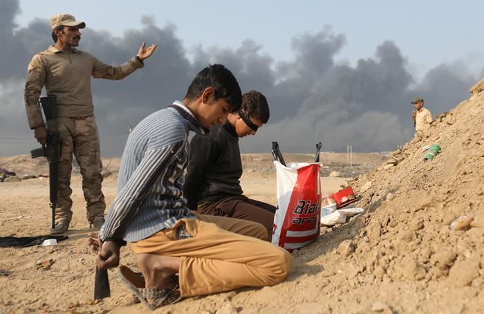 <em><br><FONT color=#000033>ทหารอิรักยืนคุมตัวชาย 2 คน ที่ต้องสงสัยว่าเป็นนักรบไอเอส ที่ด่านเมืองเคย์ยารา ทางใต้ของเมืองโมซุล หลังจากชาวบ้านหลายคนให้ข้อมูลว่านักรบไอเอสหลายคนเริ่มโกนหนวดเครา เปลี่ยนการแต่งตัว เพื่อเตรียมตัวหนีออกจากเมือง. -- Reuters/Goran Tomasevic.</font></b></em>