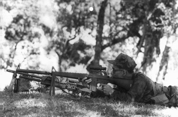 พระบาทสมเด็จพระเจ้าอยู่หัวภูมิพลอดุลยเดช ทรงพระแสงปืน M-16 ติดกล้องเล็งและท่อระงับเสียง (ท่อเก็บเสียง)