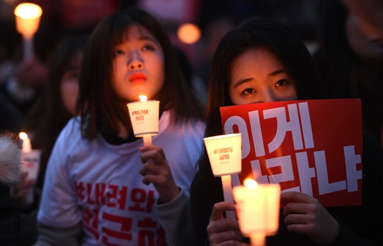 Seoul: Protesters hold candles and banners calling for the resignation of South Koreas President Park Geun-Hye during an anti-government rally in central Seoul on November 19, 2016. Tens of thousands of protestors rallied in Seoul on November 19, for the fourth in a weekly series of mass protests urging President Park Geun-Hye to resign over a corruption scandal. AFP/Jung Yeon-Je