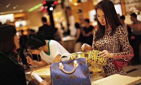 สตรีจีนคนหนึ่ง ขณะเลือกซื้อกระเป๋าหลุยส์วิตตอง ในร้านสาขาฯ ที่เซี่ยงไฮ้ (ภาพจากแฟ้มรอยเตอร์ส)