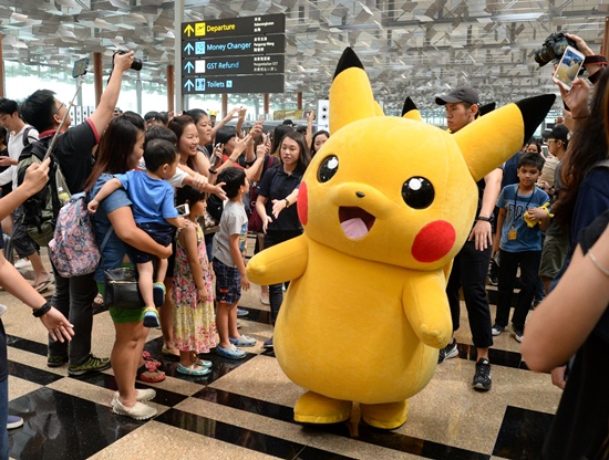 Singapore: Fans gather to watch the Pokemon Go virtual reality game mascot Pikachu parade during a promotional event at the Changi International airport terminal in Singapore on November 18, 2016. Hundreds of Pokemon fans gathered at Changi Airports Terminal 3 on November 18 to watch the Pikachu parade and Gingerbread House display which are part of the airports year-end events. AFP/Roslan Rahman