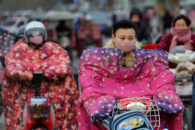 ชาวจีนสวมเสื้อแจ๊คเก็ตแบบพิเศษสำหรับผู้ขับขี่รถจักรยานยนต์ ช่วยป้องกันลม ในเมืองเหลียนอวิ๋นกั่ง มณฑลเจียงซี ภาพวันที่ 23 พ.ย. 2016 (ภาพ รอยเตอร์ส)