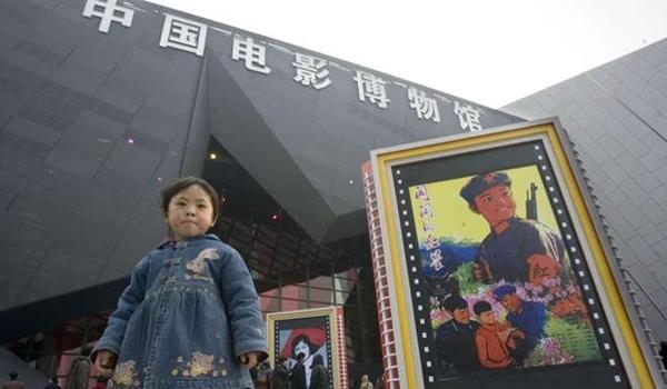 เด็กหญิงเดินผ่านโปสเตอร์ภาพยนตร์ที่จัดแสดงอยู่หน้าพิพิธภัณฑ์ภาพยนตร์แห่งประเทศจีนในกรุงปักกิ่ง (ภาพ เอพี)