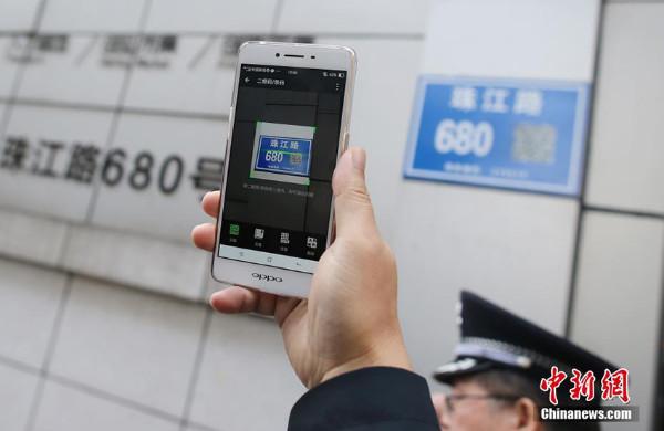 ประชาชนสามารถใช้มือถือแสกน QR code ที่อยู่บนป้ายถนน เพื่อค้นหาข้อมูลของถนน  (ภาพไชน่านิวส์ สื่อจีน)