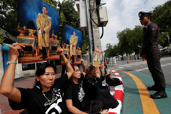 Well-wishers hold up pictures of Thailands new King Maha Vajiralongkorn Bodindradebayavarangkun before he arrives at the Grand Palace in Bangkok, Thailand, December 2, 2016. REUTERS/Chaiwat Subprasom
