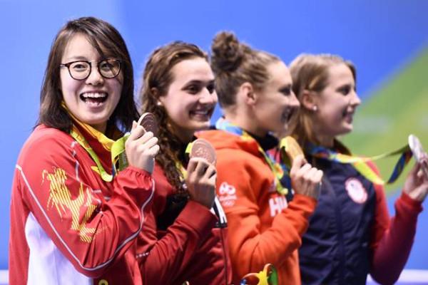 ฟู่ หยวนฮุ่ย (ซ้ายสุด) ผู้คว้าเหรียญชัยให้แก่ประเทศจีนจากการแข่งขันว่ายน้ำกรรเชียง 100 เมตร (ภาพ เอเอฟพี)