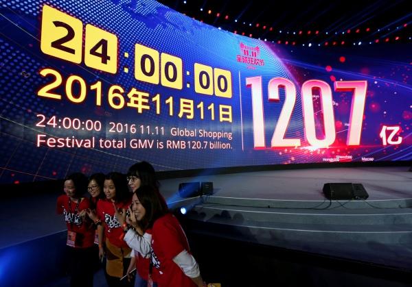 เหล่าพนักงานถ่ายภาพเฉลิมฉลองความสำเร็จอยู่ด้านหน้าจอที่แสดงยอดขายสุทธิของอาลีบาบาในวันคนโสด นครเซินเจิ้น มณฑลกวางตุ้ง วันที่ 12 พ.ย. 2559 (ภาพ รอยเตอร์ส)